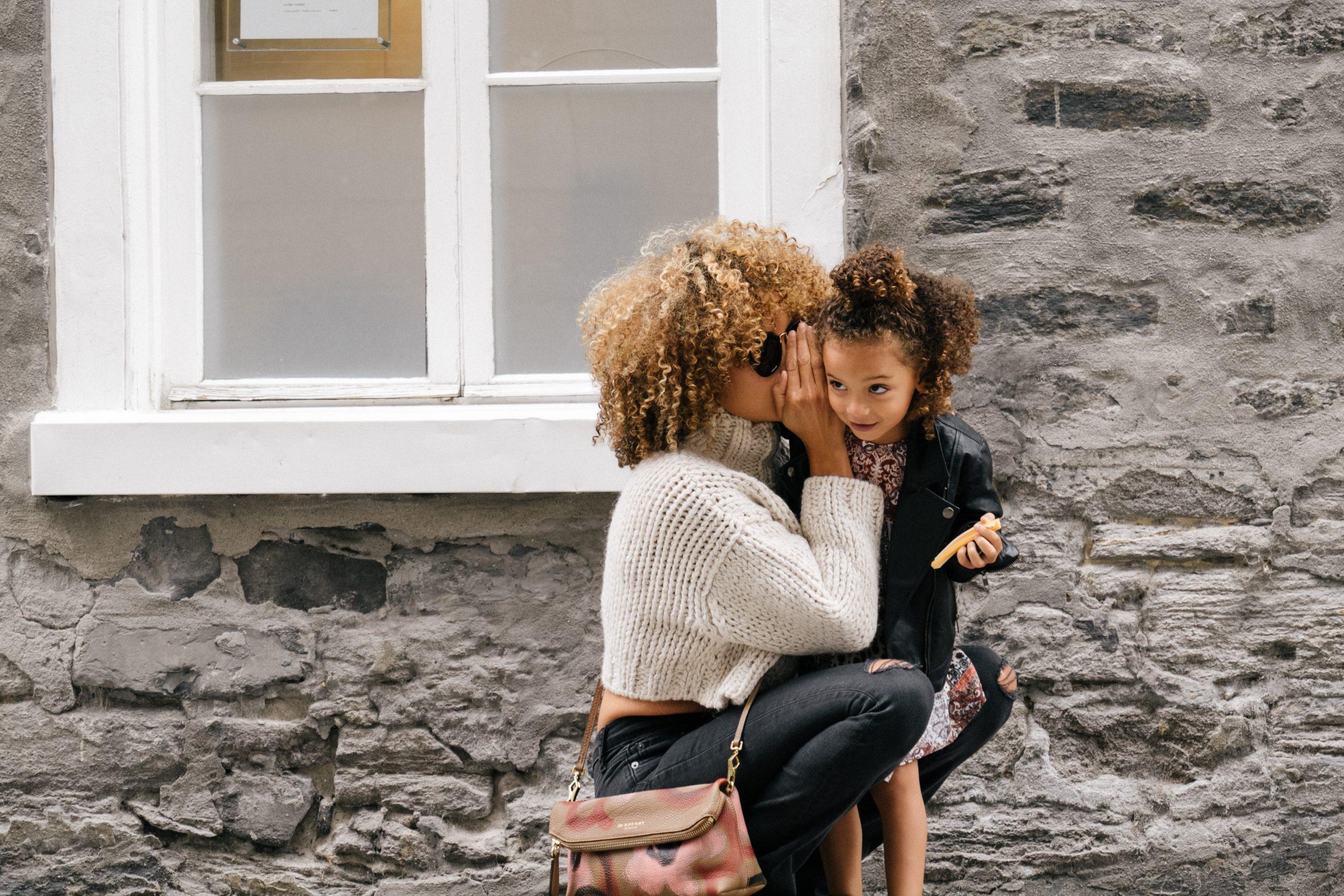 Una madre habla al oído de su hija